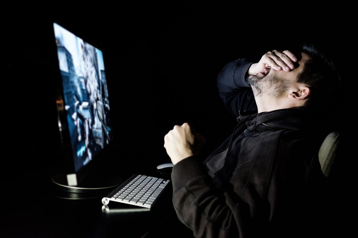 A man sitting in front of a large computer monitor. He has his right hand covering his eyes. He is making a fist with his left hand.