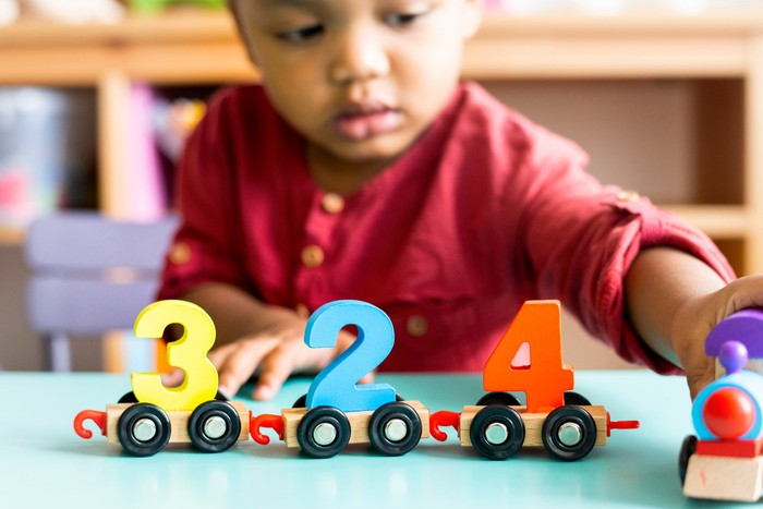 A little boy plays with a wooden toy train with numbers on each car.