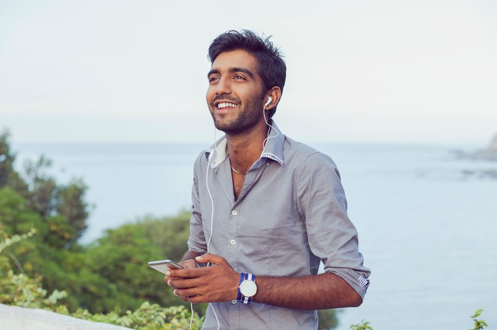 A young Indian man outside smiling while listening to music with headphones