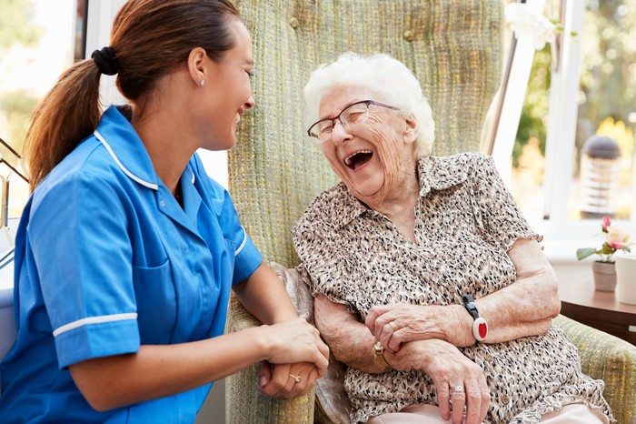 Young woman in scrubs smiling, sitting next to laughing older woman