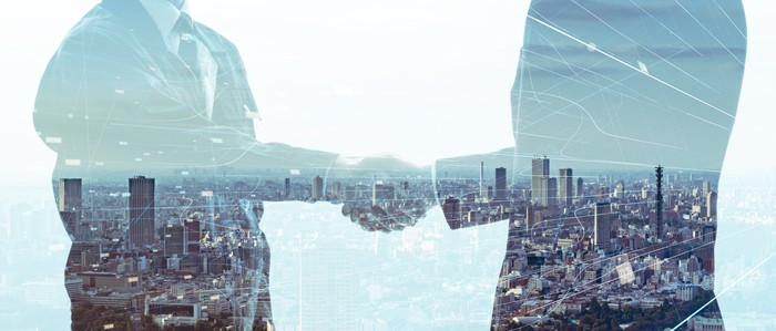 Silhouette of two business people shaking hands with cityscape superimposed on their bodies.