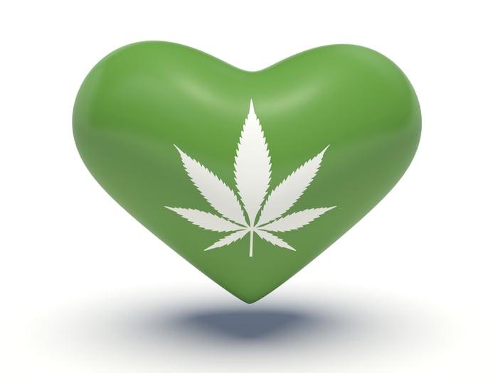 White marijuana leaf printed on a green heart.