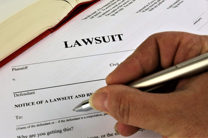 A person filling out legal lawsuit documents.