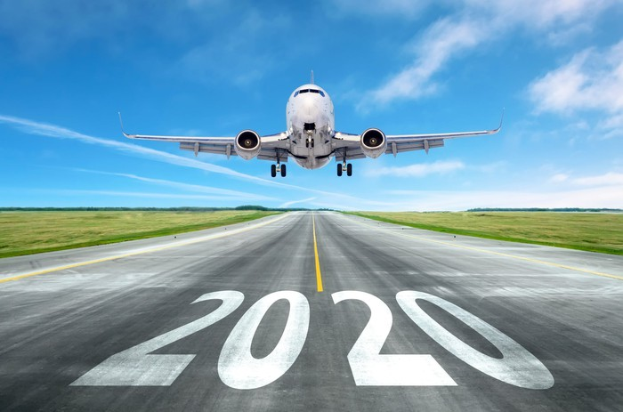 """A plane taking off from a strip with """"2020"""" written on it."""