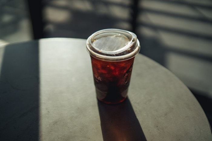 A plastic Starbucks cup with a lid resembling a toddler's sippy cup