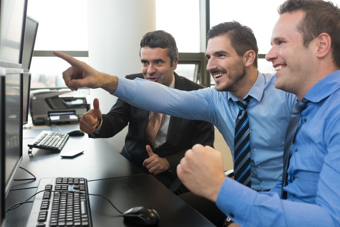 Three traders pointing at a computer screen and smiling