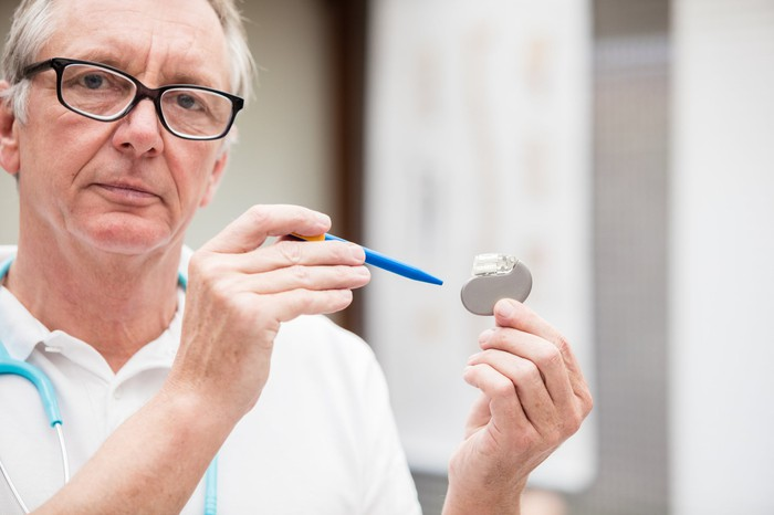 A medical doctor holding a traditional pacemaker in his hand.