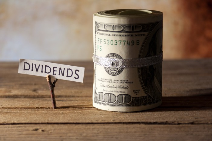 """A wooden table with a little note that says """"dividends"""" sticking up through the boards sitting next to a roll of dollar bills."""