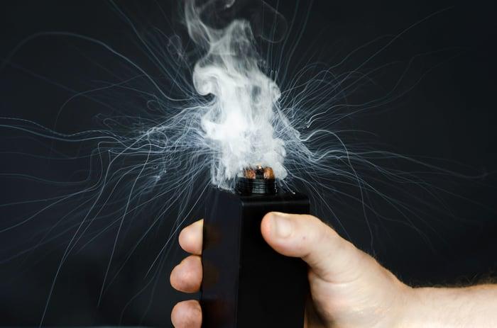 A hand activating a vaporizer.