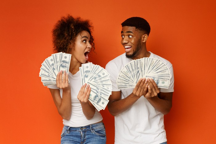 A young man and woman hold fanned-out cash in both their hands with astonished expressions.