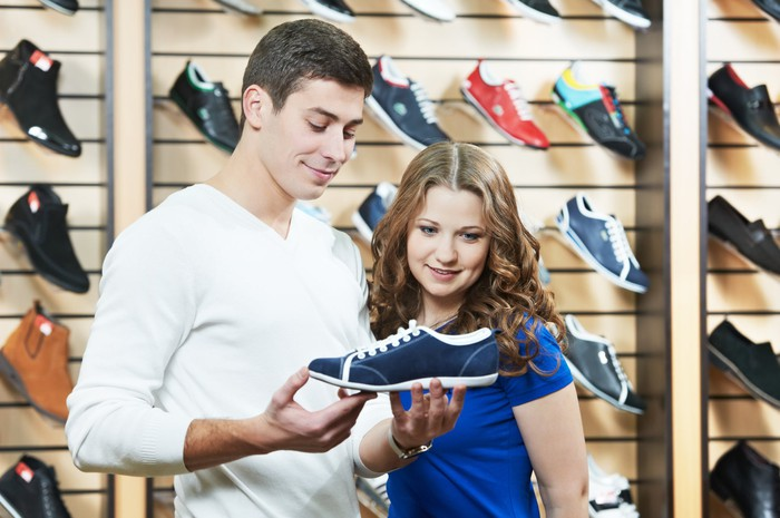 Consumers holding up and closely examining a shoe inside of a shoe store.