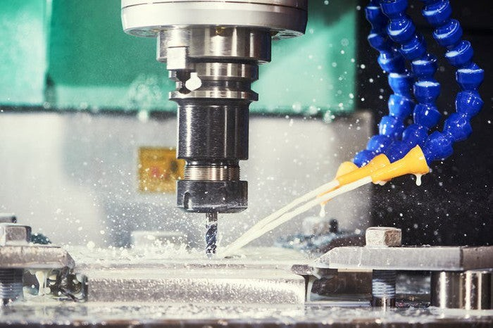 Close-up of a CNC machine drilling a hole in metal.