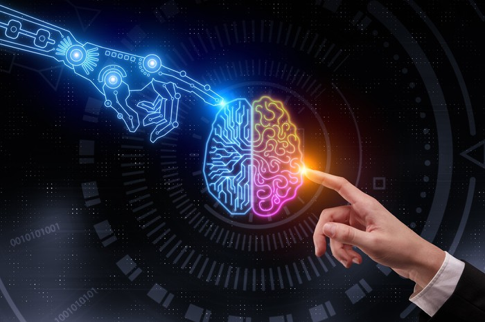 A robot hand and a human hand touch two halves of a brain.