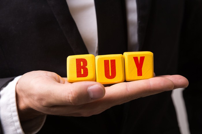 """A businessman holding a set of large yellow blocks that spell out the word """"buy"""" in red capital letters."""