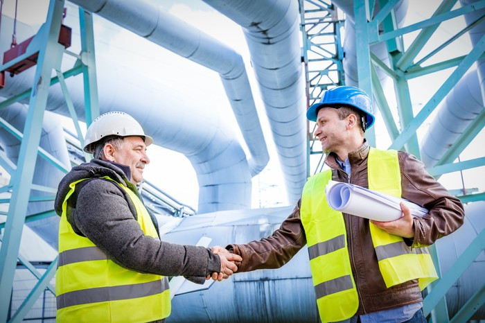 Two men shaking hands in front of energy infrastructure