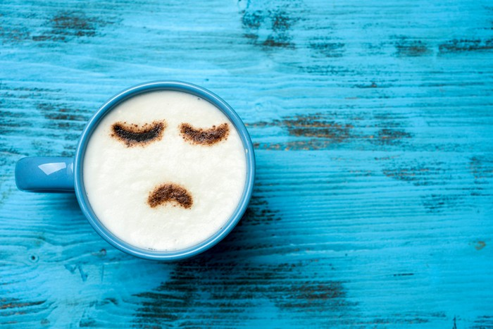 high-angle shot of a blue cup of cappuccino with a sad face drawn with cocoa powder on its milk foam