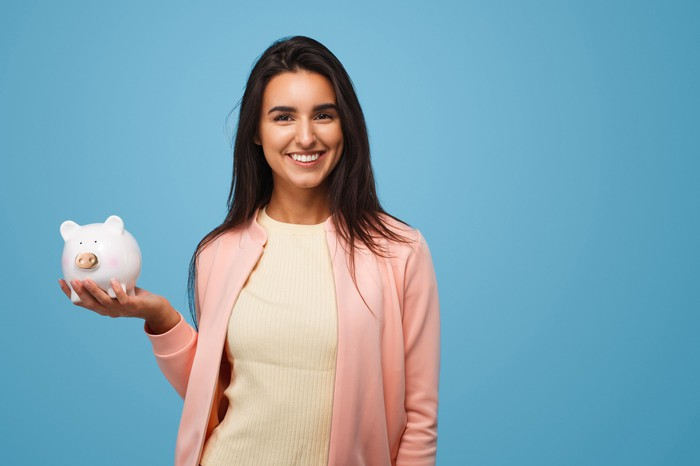 Woman smiling and holding piggy bank.
