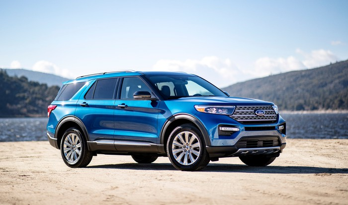 A blue 2020 Ford Explorer, a seven-passenger crossover SUV, parked on sandy ground with a body of water and mountains in the background