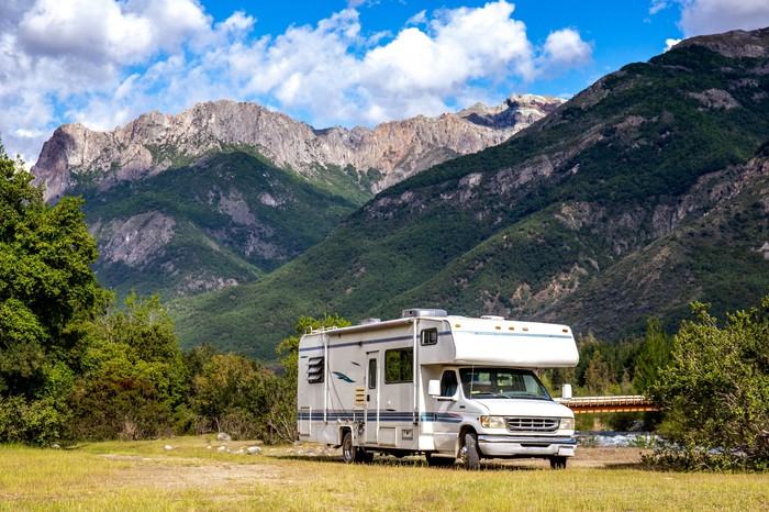 Mobile home in front of mountains.