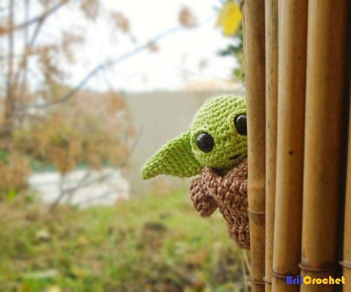 Baby Yoda hiding behind a curtain