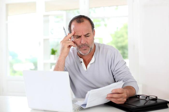 Older man looking at documents feeling worried