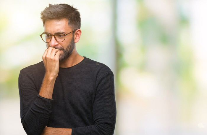 Bespectacled man biting his nails