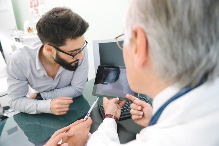 A patients and a doctor going over a lung scan.
