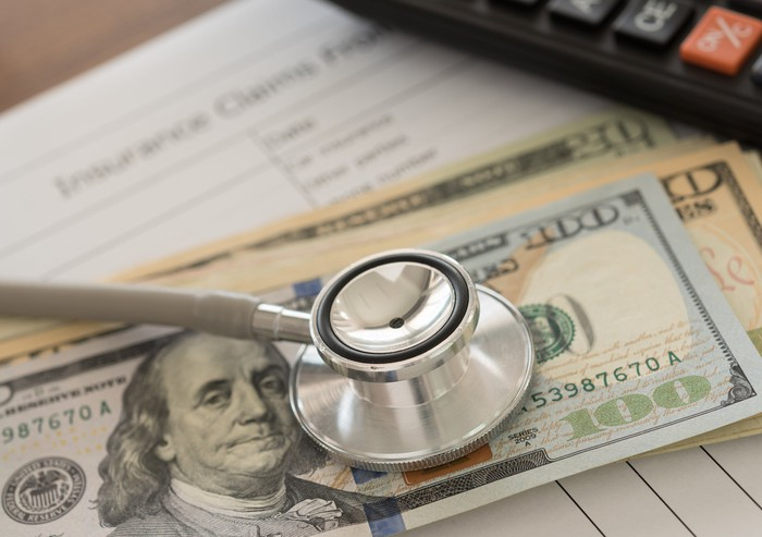 Stethoscope atop US currency and insurance claim form.