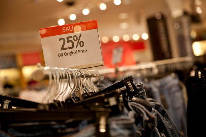 Clothes rack holding new jeans with a sign advertising a 25% off sale.