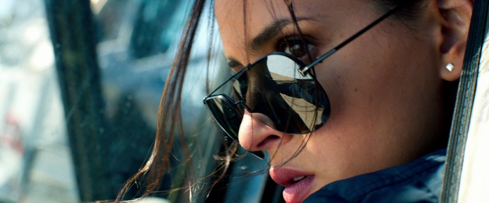 A closeup of a woman's face as she peers over her sunglasses with her hair hanging in her face.