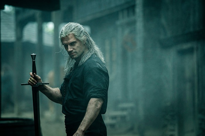 A muscular man with long, white hair dressed in black brandishing a sword.