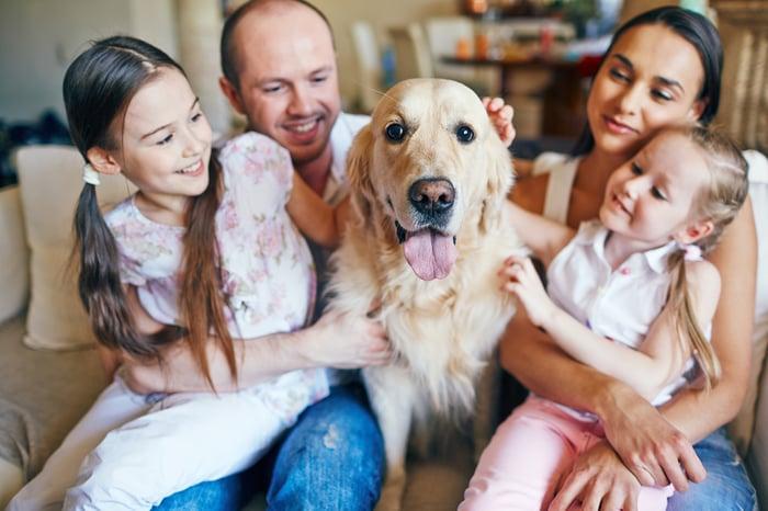 Una familia feliz de cuatro personas sentada en un sofá, con su perro en el medio.