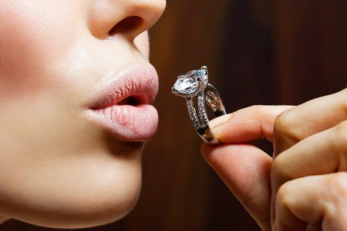 A woman kisses a diamond ring.