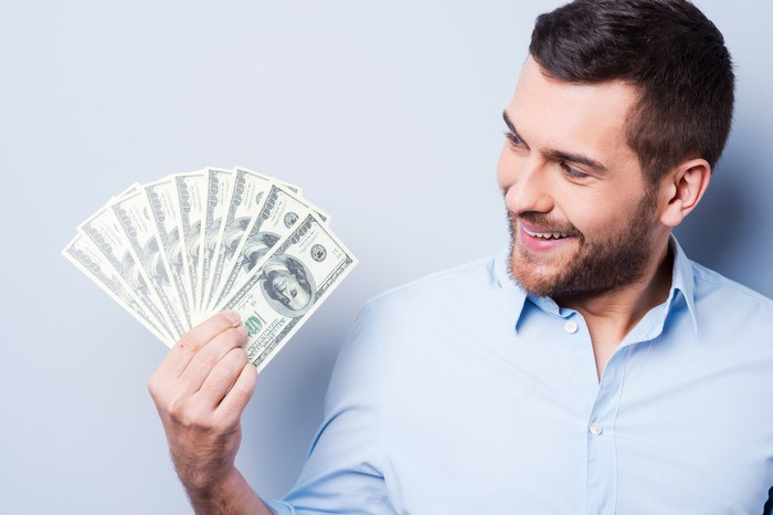 A man smiles at a fanned out stack of hundred dollar bills in his hand.