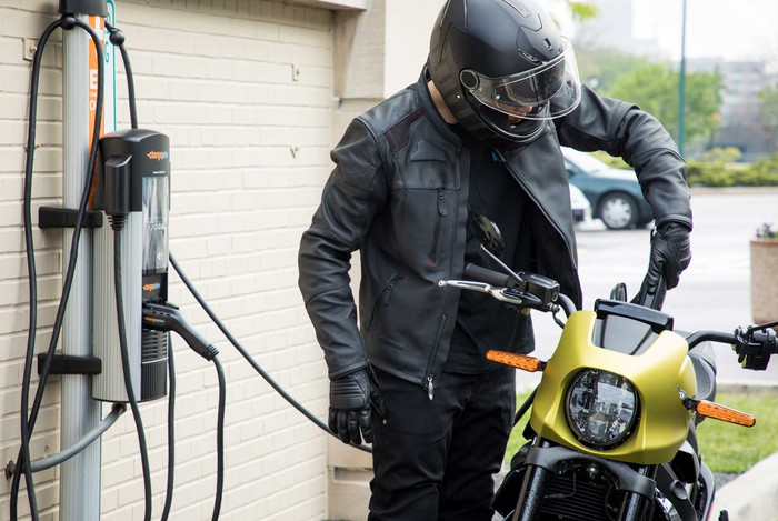 Motorcyclist using a fast charge charging station for the LiveWire