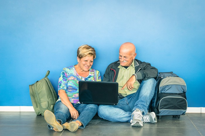 A happy older couple sitting on a floor with travel bags.