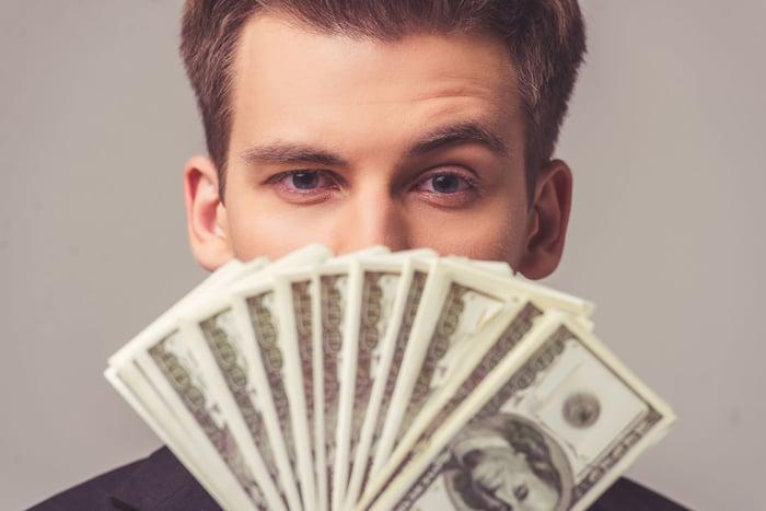 Man holding lots of hundred dollar bills