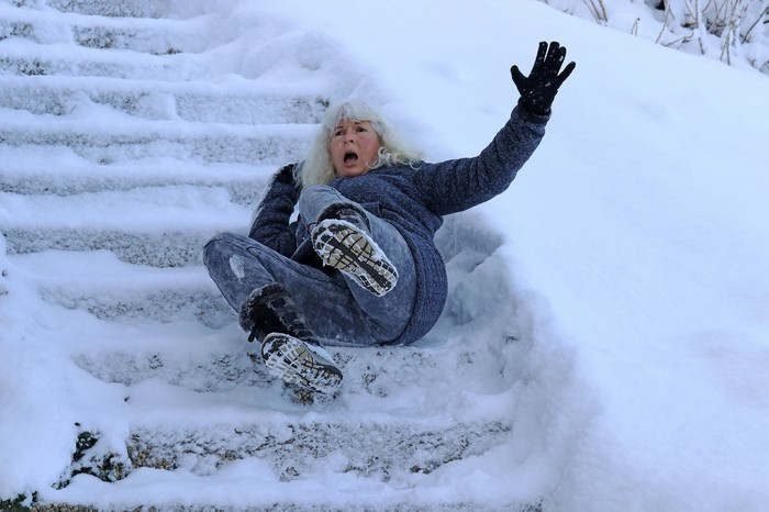 An older woman falling down a flight of snowy steps outdoors
