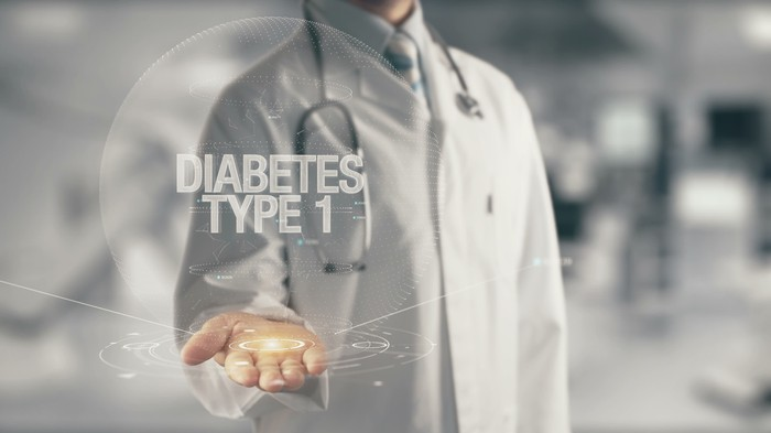 "Man in white coat with stethoscope around his neck holding out his palm with an image of the words ""Diabetes Type 1"" appearing above his hand"