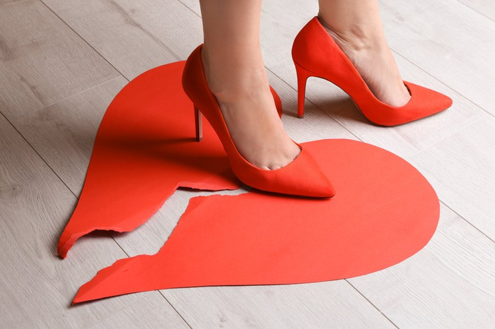 Woman in red high heels stepping on a broken heart.