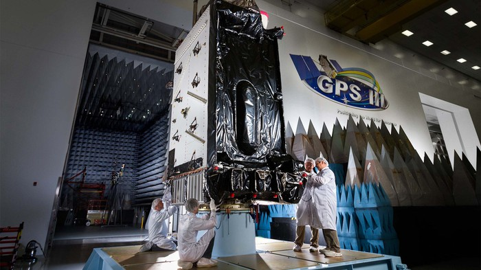 Engineers work on a GPS satellite in a production facility.
