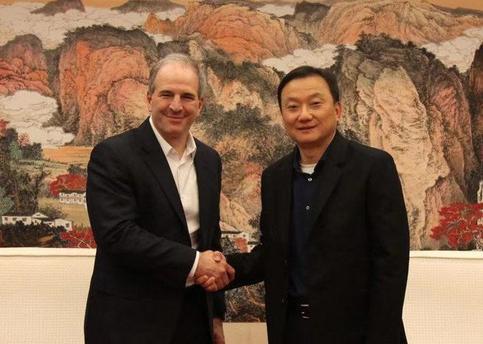 Jim Magats and Larry Wang smiling and shaking hands