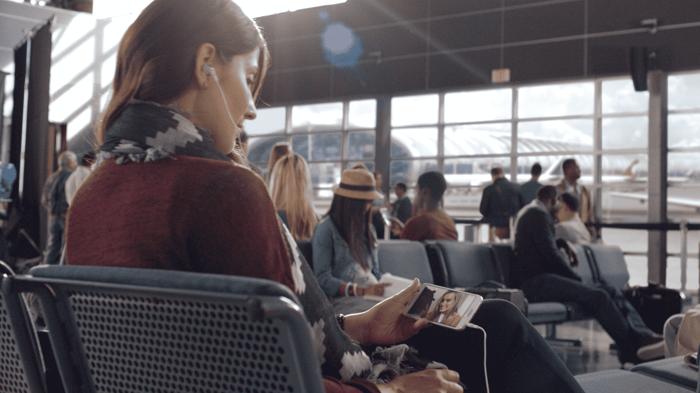 A woman watching Netflix on a smartphone.