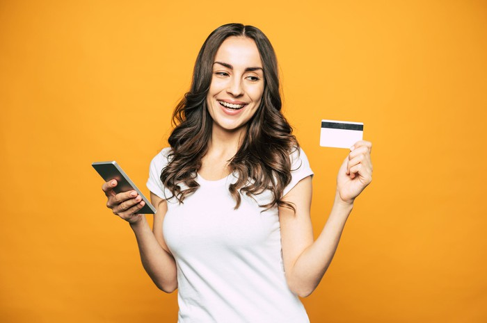 A young woman smiles and holds a credit card in one hand and her cell phone in the other.