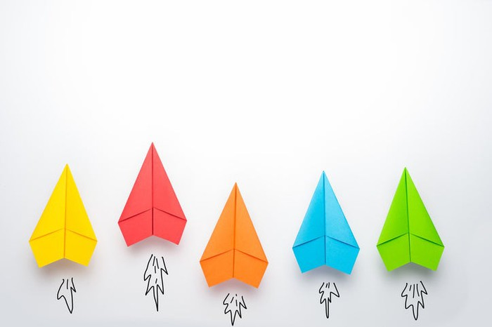 Five paper airplanes, each a different color, pointing up.