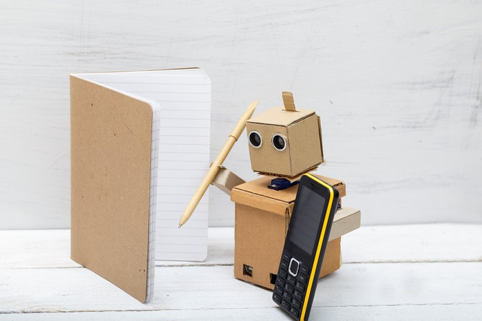 A robot made of cardboard holding a pencil and a phone, standing in front of an open notebook.
