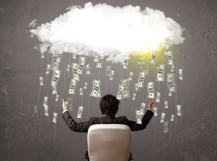 Cash rains on a seated businessman.