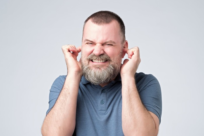 Man grimacing with his fingers in his ears