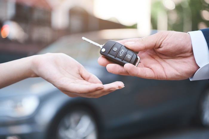 Close-up of a car salesman handing the keys to a car to a customer.