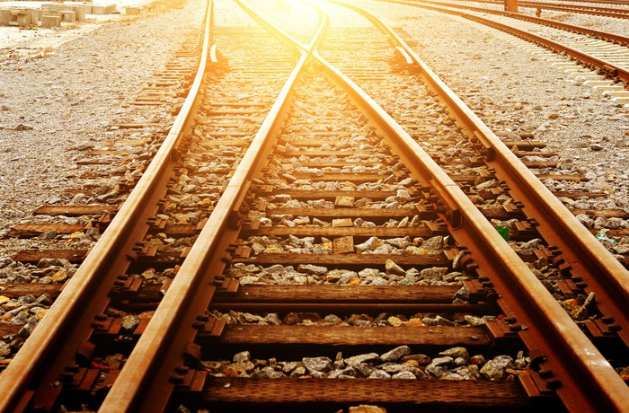 Railroad tracks with the sun shining on them.
